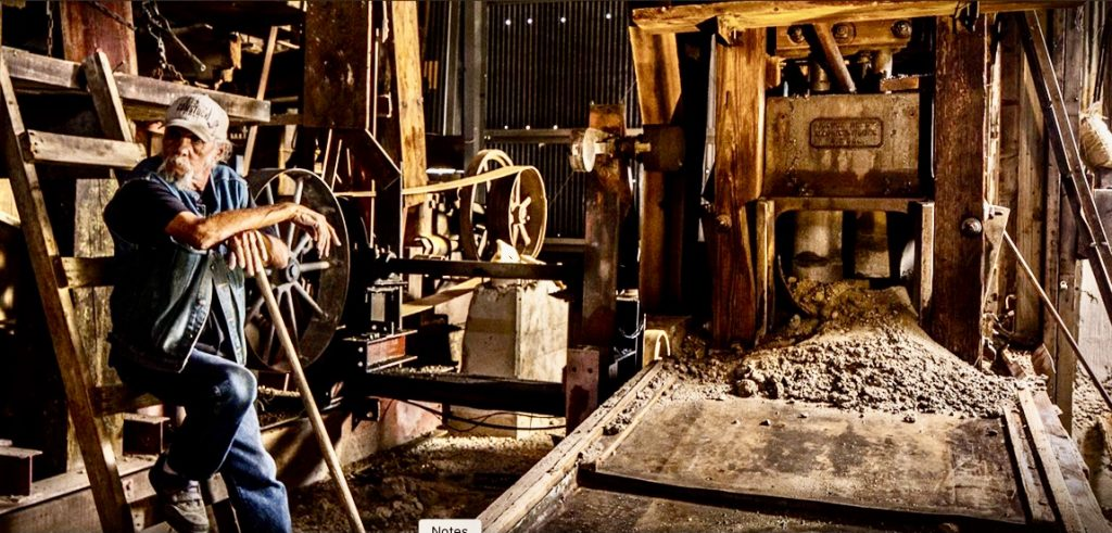old timer sitting by mining equipment